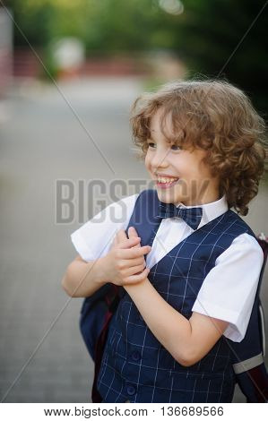 Cute little schoolboy standing on the sidewalk. It is elegantly dressed. Behind the boy a school backpack. The disciple has crossed hands on a breast and smiles