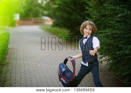 Cute little schoolboy waving his briefcase in the schoolyard. The boy has blond curly hair and blue eyes. He looks into the camera with an angry smile.