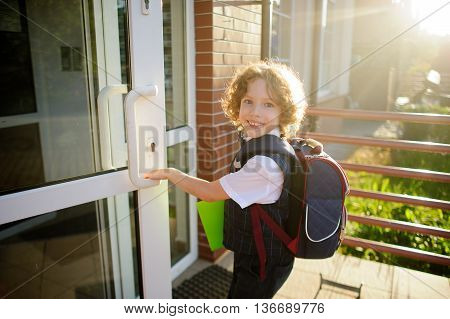 Little Kinky schoolboy opens a school door. The boy's pretty face. Behind the backpack in the hands of bright green folder. Schoolboy looks into the camera and smiles.