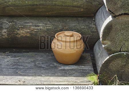 brown vintage pot in old blockhouse corner close up