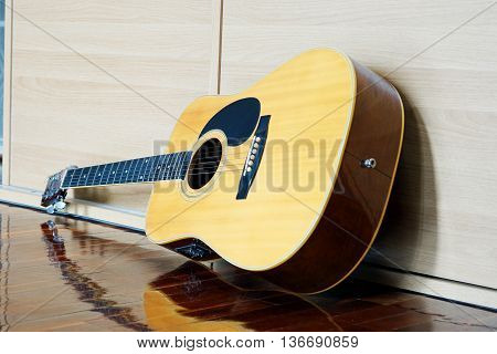Electric Guitar lying on wooden cabinet in the room