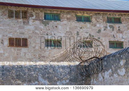 FREMANTLE,WA,AUSTRALIA-JUNE 1,2016:  Limestone exterior walls and razor wire security fencing at the Fremantle Prison in Fremantle, Western Australia.