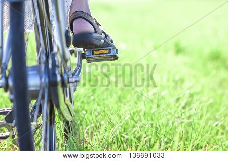 Womans foot on bicycle pedal on green grass closeup