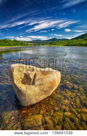 Mountain river stream of water in the rocks with blue sky. Clear river with rocks. Stone foreground