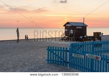 Palanga Lithuania - June 13: View At The Palanga Sandy Beach With Lifeguard House With Couple Of Tou