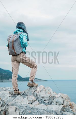 Unrecognizable explorer young woman with backpack standing on peak of cliff and enjoying view of sea in summer