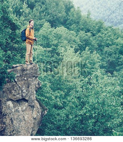 Hiker with backpack and trekking poles standing on edge of cliff and enjoying view of nature in summer outdoor