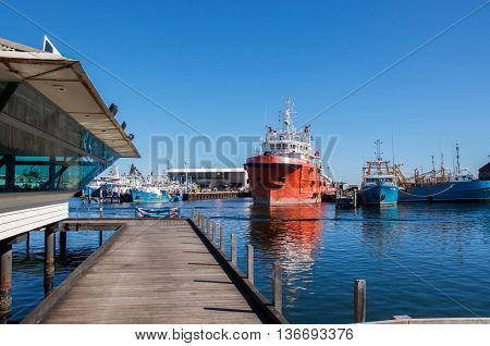 FREMANTLE,WA,AUSTRALIA-JUNE 1,2016: Elevated walkway and commercial fishing boats in the Fremantle Fishing Boat Harbour under a blue sky in Fremantle, Western Australia.