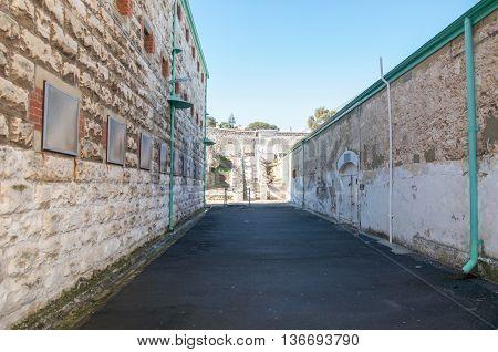 FREMANTLE,WA,AUSTRALIA-JUNE 13,2016: View through exterior limestone brick walls at the Fremantle Prison under a blue sky in Fremantle, Western Australia.
