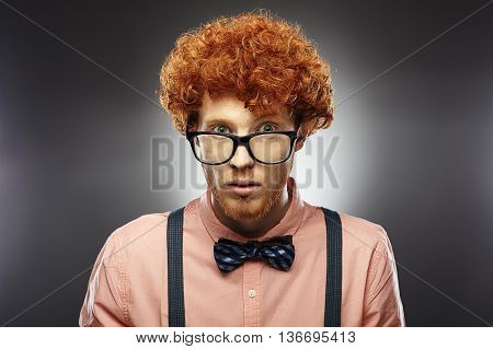 Red Hair Models. Bearded man. Portrait. Young Redhead man curly in glasses, bow tie and suspenders on gray background.