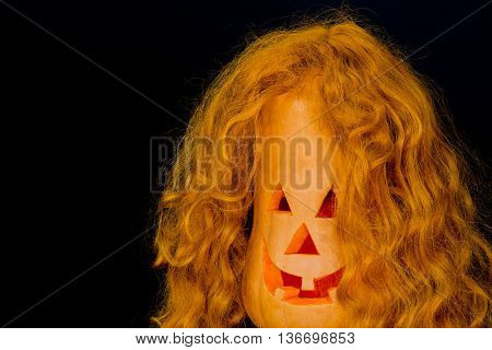 Halloween pumpkins with very scary face and with red hair, burning candle on black background. With your place for the text. Halloween costumes