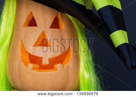 Scary Halloween pumpkins in hat isolated on a black background close up. Scary glowing faces. Halloween ideas .