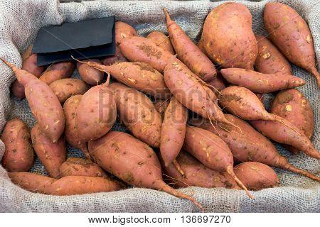 Batata. Raw sweet potatoes in a box.