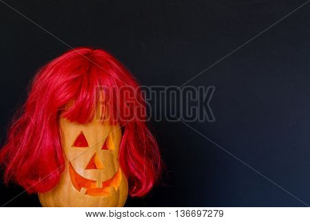 Scary Halloween pumpkins with red hair isolated on a black background. Scary glowing faces. Halloween ideas . With your place for the text.