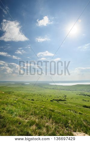 Photo of beautiful landscape with grassy land and lake under sunny skies