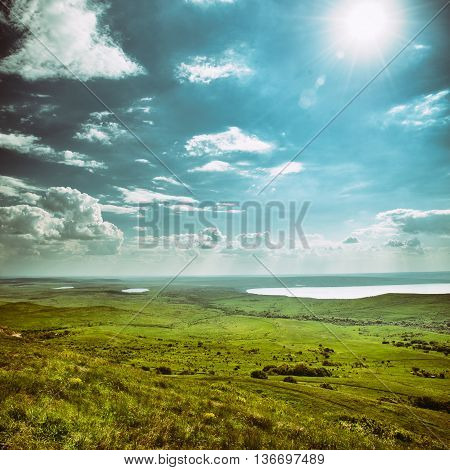 Photo of beautiful landscape with grassy land and lake under sunny skies in vintage style