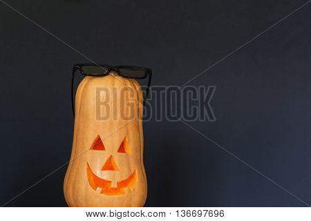 Scary Halloween pumpkin with black sunglasses isolated on a black background. Scary glowing faces. Halloween ideas . With your place for the text.