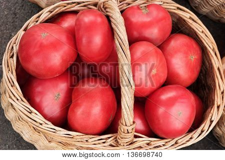 Big tomatoes in wooden basket. Top view