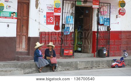Magdalena Cajamarca Peru - June 28 2016: Two women wearing sombreros sit on curb talking in front of small store in Magdalena Cajamarca Peru on June 28 2016.