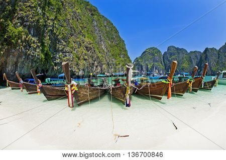 Thailand beach seascape with ring of steep limestone hills and traditional bright longtail boats parking Maya Bay Ko Phi Phi Lee island Phi Phi archipelago part of Krabi Province Andaman Sea