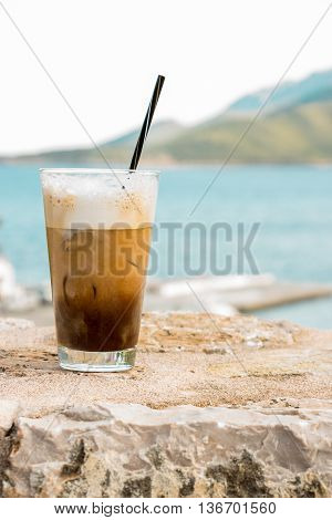 Left cup of coffee with ice cream right seascape on the background of the sea. Coffe with ice and cream. Vertical. Daylight.