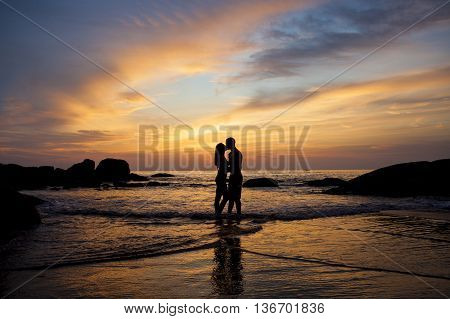 Couple kissing on the beach with a beautiful sunset in background