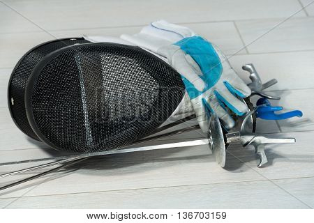 Fencing foil equipment. Three fencing foils with pistol grip (sporting weapon) a fencing mask and a blue and white glove on floor