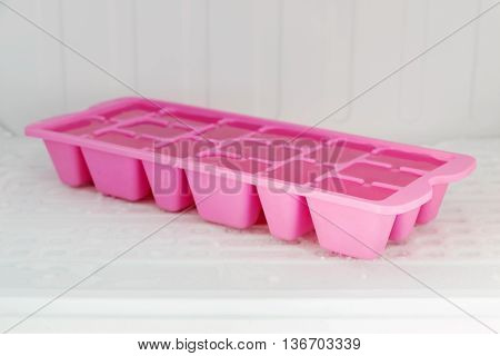 Colorful plastic ice tray in the freezer compartment of the refrigerator.