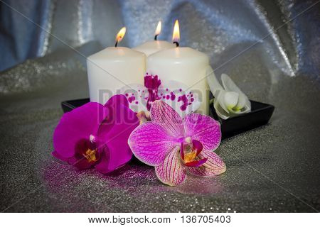 Different phalaenopsis flowers (orchid) and burning candles on light silver sparkling background with bokeh. Photo toned and with vignette