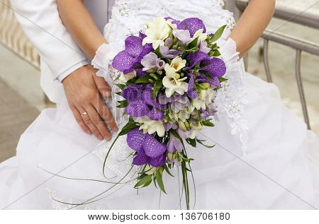 beautiful wedding bouquet of orchids in the hands of the bride