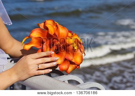 beautiful wedding bouquet of Calla lilies in the hands of the bride