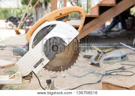Electric circular saw tool in construction built wood staircase