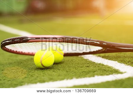 Close up of two tennis balls under racquet on lawn