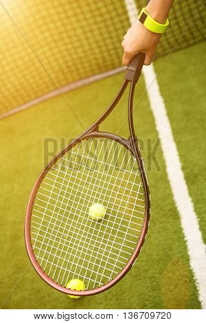 Close up of arm of tennis player holding racket. Woman is playing tennis on professional court. Tracker on her wrist. Balls and net on background