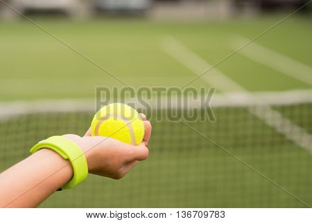 Close up of female hand holding yellow ball. Tennis court with net on background. Athlete has tracker on arm