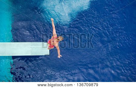 Lady springboard diver preparing to dive from the springboard into the swimming pool
