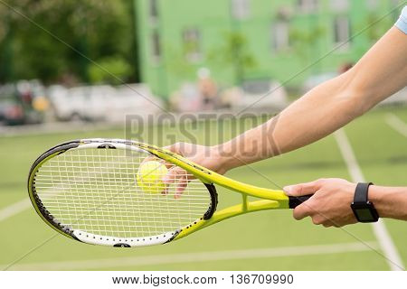 Close up of young athlete arms beating a tennis ball by racket. Man is standing in stadium