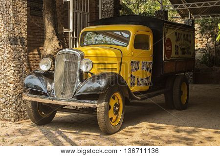 Hartbeespoort,  South Africa -  October 10, 2015: Yellow old model Chevrolet pickup truck in the patio of ancient cafe Tan Malie Se Winkel 1921. Vintage car style.