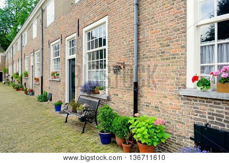 Row of historic houses with masonry brick facades in the Begijnhof in the Dutch city of Breda. This beguinage is the oldest beguinage in the Netherlands.