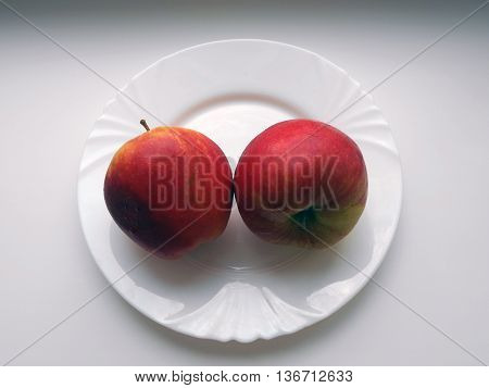 Apples lie on a plate. Apples are grown in the garden. The apples are large, red.