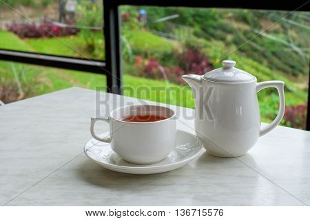White cup of tea and teapot on white marble table in tea shop at Cameron Highlands Malaysia.