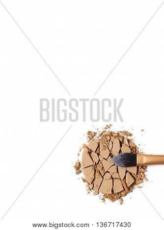 Smashed foundation face powder with make up brush isolated on a white background