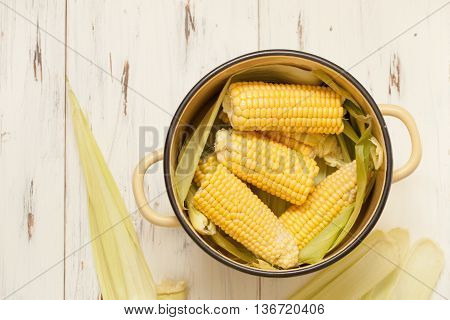 Raw Cobs Of Young Corn With Leaves On A Wooden Table