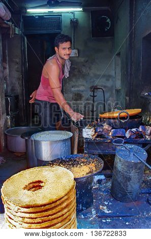 Unidentified Street Vendor Cooks At A  Market