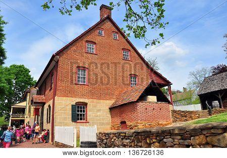 Old Salem North Carolina - April 21 2016: School children visiting the historic C. Winkler Bakery built in 1800 with its large exterior bake oven *