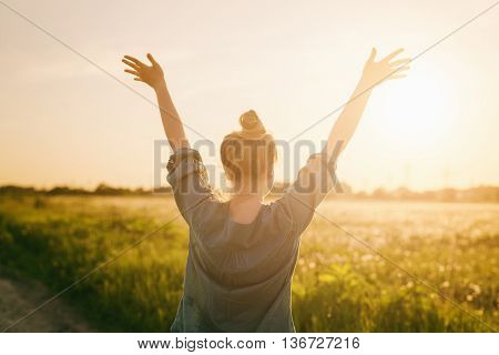 female teen girl stand feel freedom with arms stretched to the sky, sunset light