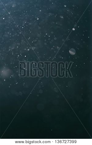 real backlit dust particles with blue toned flare, vertical backdrop
