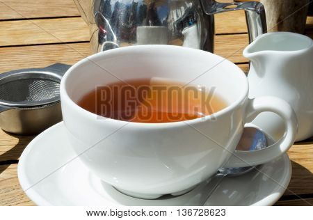 Cup of tea on wooden table with mug, pot and strainer