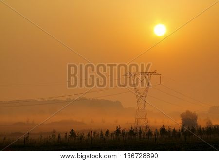 Landscape with electricity transmission pylon in morning mist at sunrise. Poland, Holy Cross Mountains.
