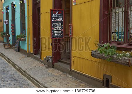 VALPARAISO, CHILE - JULY 1, 2016: Colourful houses and cafes lining a narrow street in the UNESCO World Heritage city of Valparaiso on the Pacific Coast of Chile.